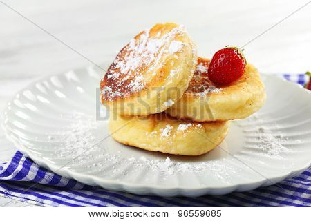 Fritters of cottage cheese with strawberry and sugar in plate on table, closeup