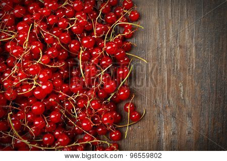 Heap of fresh currant on wooden background