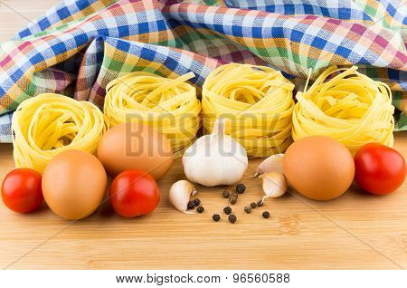 Pasta Nests, Eggs And Tomatoes On Background Of Towels