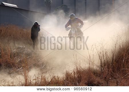 Motorbike Airborne Over Bump In Dust On Sand Track During Rally Race.
