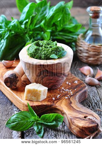 homemade pesto made of organic basil on the board of olives with parmesan and garlic