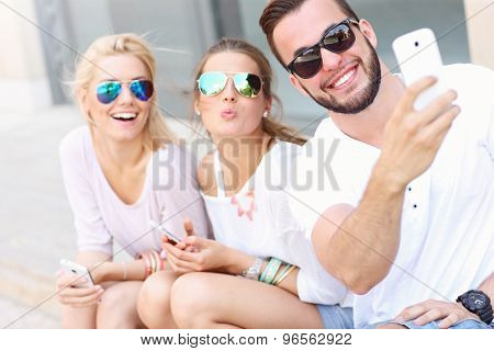 A picture of a group of friends taking selfie in the city