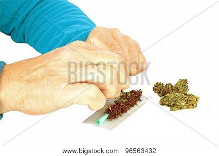 Man making a joint from marijuana