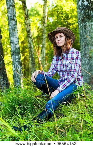 Cowboy girl sitting in the green summer forest