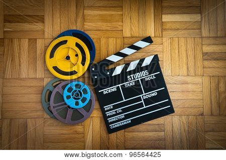 Movie Clapper Board And Film Reel On Wooden Floor