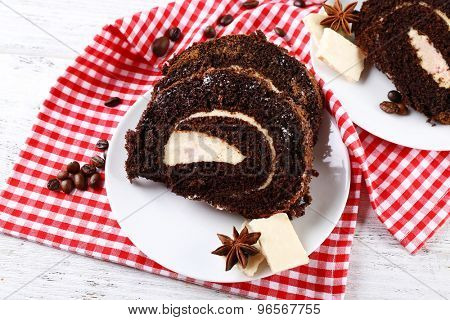 Delicious chocolate roll in white saucer on wooden table with checkered napkin, closeup