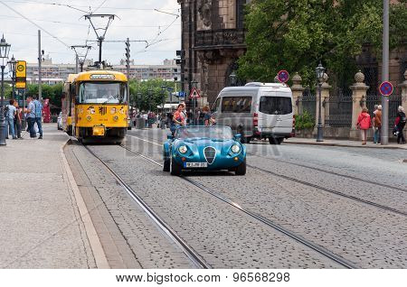 Dresden, Germany - July 2012 - Street view with yellow train, sport car and tourists