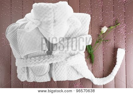 Bathrobe and slippers on wooden table, top view