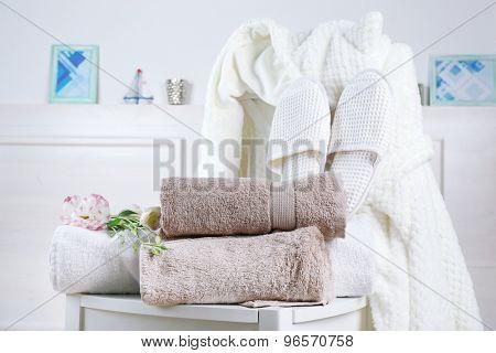 Bath set with white bathrobe on chair, indoors