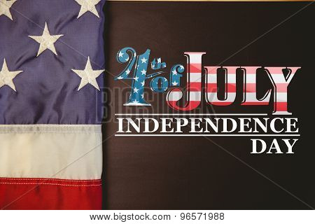 Independence day graphic against american flag on chalkboard