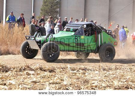 Custom Twin Seater Rally Buggy Kicking Up Trail Of Dust On Sand Track During Rally Race.
