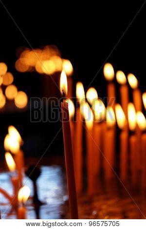 Burning church candles in dark