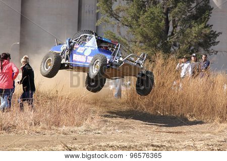 Custom Twin Seater Rally Buggy Airborne Over Bump On Sand Track During Rally Race.