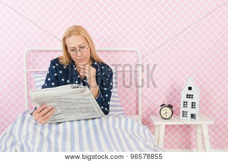 Woman of mature age reading daily newspapers in bed