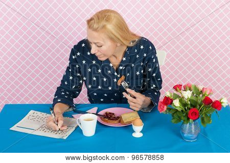 Mature woman making crossword puzzle in newspapers in while having breakfast