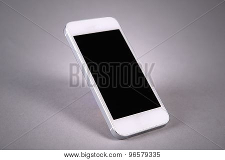 Modern touchscreen mobile phone on gray background