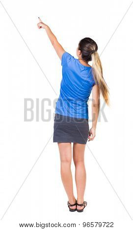 Back view of  pointing woman. beautiful girl. Rear view people collection.  backside view of person.  Girl in a gray skirt and blue T-shirt shows a finger of his right hand up and left.