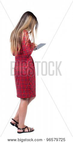 back view of standing young beautiful  girl with tablet computer in the hands of. girl  watching.   Isolated over white background.  Long-haired girl in a red plaid dress delves into the tablet