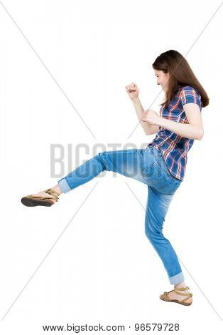skinny woman funny fights waving his arms and legs. Isolated over white background. A young girl in a checkered blue with red stripes hit the right foot.