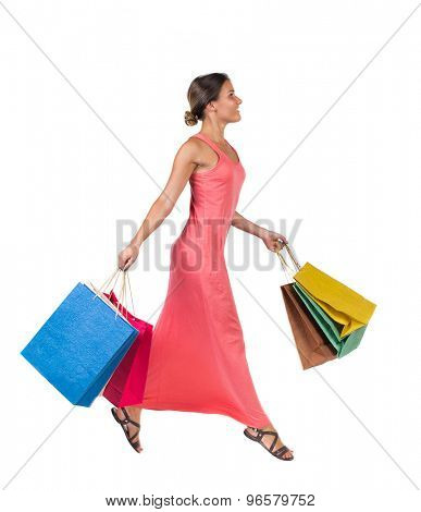 side view of a woman jumping with shopping bags. beautiful brunette girl in motion.  backside view of person. girl in a light red dress jumping ambled carrying a paper shopping bags.