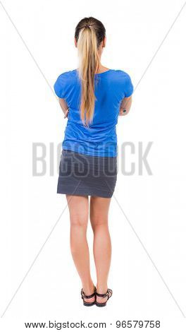 back view of standing young beautiful  woman.  girl  watching. Rear view people collection.  Isolated over white background. Girl in a gray skirt and blue shirt stands with his arms crossed.