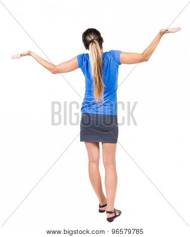Back view Beautiful woman in dress looking at wall and Holds  hand up. young blonde girl standing. Isolated over white background. Girl in a gray skirt and blue shirt throws up his hands in surprise.
