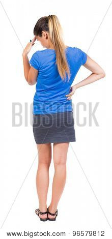 back view young beautiful girl standing in thoughtful pose. Rear view people collection. Isolated over white background. Girl in a gray skirt and blue shirt is resting his hand on forehead in thought.