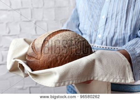 Woman holding tasty fresh bread, close up