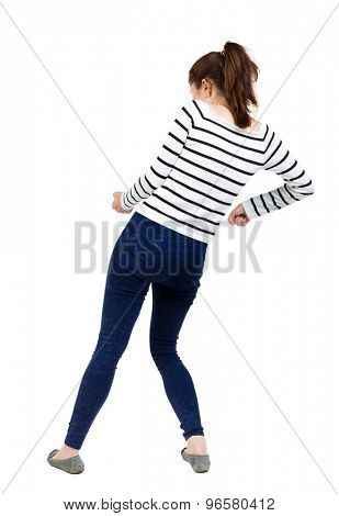 back view of standing girl pulling a rope from the top or cling to something. girl  watching.  backside view of person.  Isolated over white background. French vests and tight pants pulling a rope