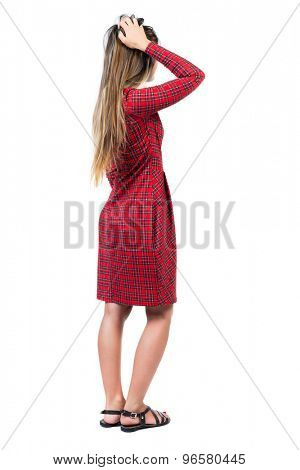 back view of young beautiful  woman scratching his head. Rear view people collection.   Isolated over white background. Long-haired girl in a red plaid dress scratching his head with his right hand.