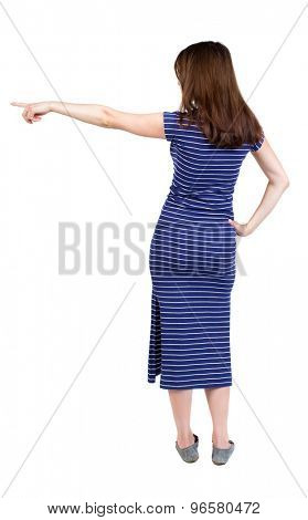 Back view pointing woman. beautiful girl. Rear view people collection.  backside view person. Girl in a blue striped dress standing and shows his right hand in his right side.