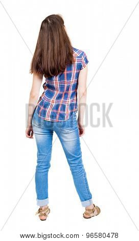 back view of standing young beautiful  woman in jeans. girl  watching. Rear view people collection. A young girl in a checkered blue shirt is looking up and looking into the distance.
