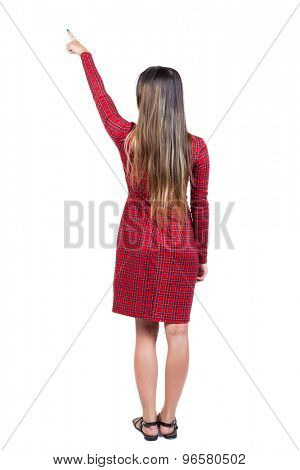 Back view of  pointing woman. beautiful girl. Rear view people collection.  backside view of person.   Long-haired girl in a red plaid dress standing shows a finger up to the right.