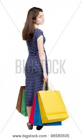 back view of going  woman  in  dress woman with shopping bags . beautiful brunette girl in motion.   Isolated over white background. Girl in a blue striped dress carries colorful shopping bags.