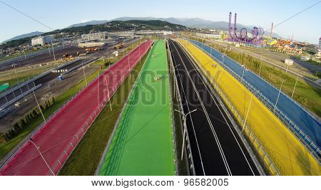RUSSIA, SOCHI - JUL 28, 2014: Five color pedestrians bridges near Sochi-park and racing stadium at summer day. Aerial view. Photo with noise from action camera