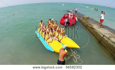 RUSSIA, SOCHI - JUN 20, 2014: People smile and wave hands before ride on inflatable banana at summer sunny day. Aerial view. Photo with noise from action camera.