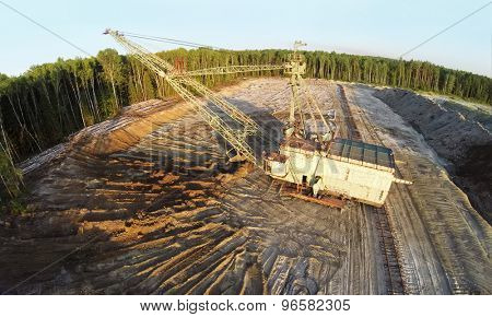 RUSSIA, VOSKRESENSK - JUL 1, 2014: Excavator ladles sand at sandpit near forest during sunset. Aerial view. Photo with noise from action camera.