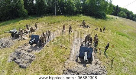 RUSSIA, MOSCOW - JUL 12, 2014: Soldiers in uniform of Soviet Army of World War II stand near three guns on battle field at spring sunny day. Aerial view. Photo with noise from action camera.