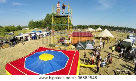 RUSSIA, NELIDOVO - JUL 12, 2014: Young boy jumps from tower to inflated deck during fair at sunny summer day. Aerial view. Photo with noise from action camera