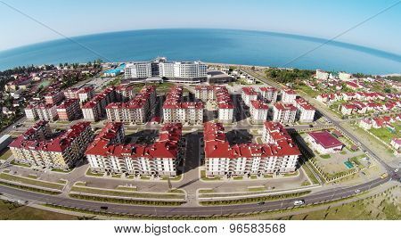 RUSSIA, SOCHI - JUL 30, 2014: Street traffic near town-hotel Barhatnye Sezony and hotel Radisson Blu on sea shore at summer sunny day. Aerial view. Photo with noise from action camera.