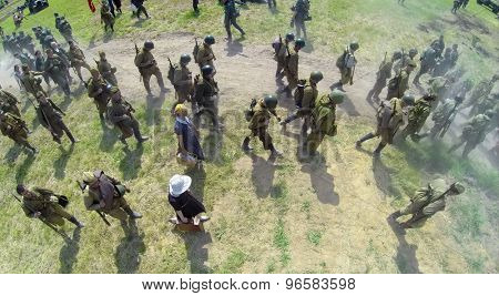 RUSSIA, NELIDOVO - JUL 12, 2014: Civilians and soldiers in uniform of soviet army walk in dust on road during reconstruction Battlefield at sunny day. Aerial view. Photo with noise from action camera