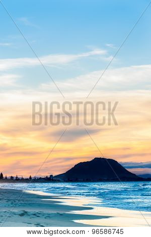Setting Sun Casts Blue Tinge On Water And Beach And Orange Cloud Silhouetting The Landmark Mountain