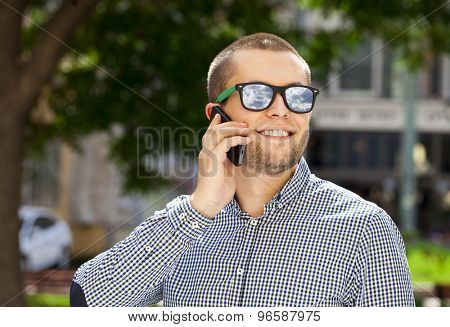 Happy young men calling by phone in summer street