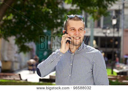 happy men calling by phone in summer street