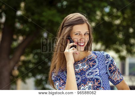 Happy beautiful woman calling by phone in a summer street
