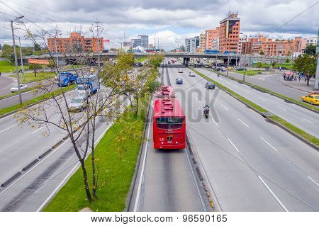 Great overview shot of main road portraing red public transportation Transmilenio, background brick