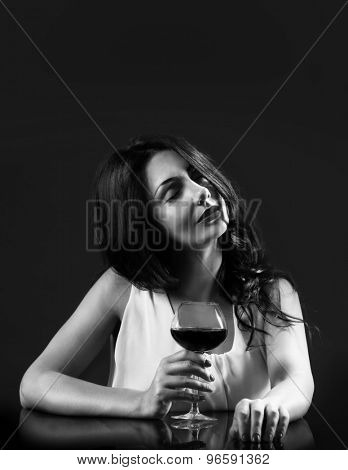 Pretty young woman with wineglass in shades of grey