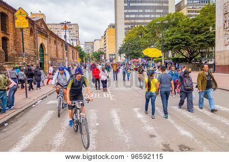 Unidentified hispanic pedestrians and cyclists moving through city street Candelaria area Bogota