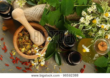 Herbs, berries and flowers with mortar, on wooden table background