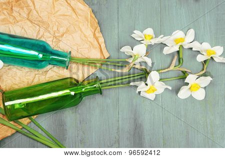 Beautiful daffodils in vases on wooden background
